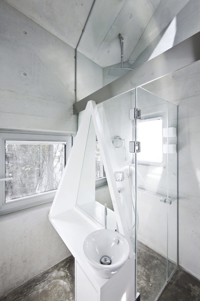 A white vessel sink fitted on a unique shaped vanity is fixed into the glass enclosure of the walk-in shower in this contemporary bathroom. It has concrete flooring and vaulted ceiling.