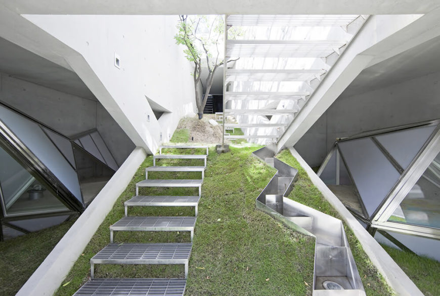 Leading up from the ground floor, even the entry stairs are coated in moss and dotted with trees. The metal stairs share this green space with a snaking line of lighting encasements, holding upward facing bulbs.
