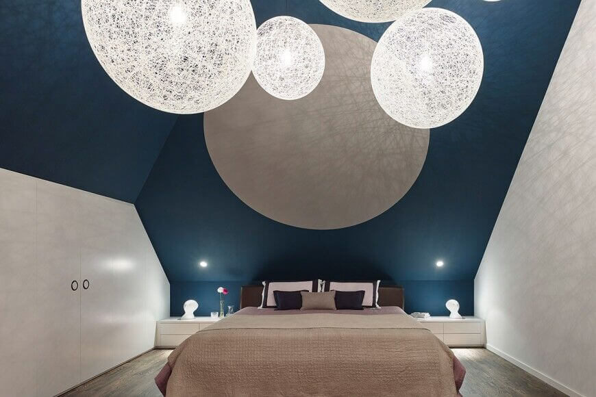 A minimalist bedroom with just a few accent pillows and two bedside tables, this space is brought to life by the peculiar angled ceiling and large orb lighting. The blue colored wall is what gives this room its depth.