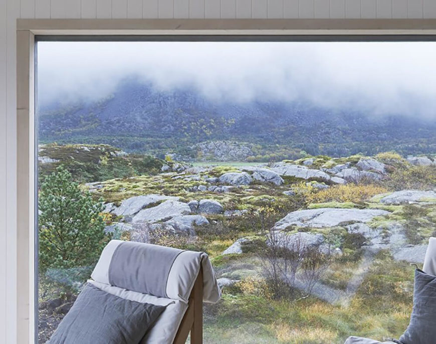 Over the natural wood chairs and through the vast living room window, se can see the mountains rising in the distance, across acres of rocky terrain. The windows are framed in light natural wood for high contrast.