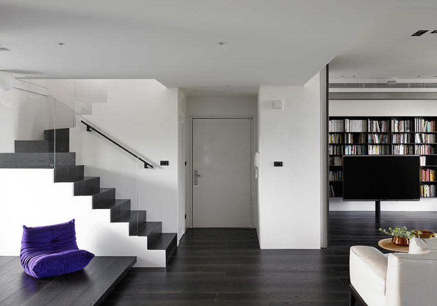 White walls were chosen as the backdrop to this stunning home remodel to allow the subtle additions of color to pop throughout the home. Black flooring is used throughout the main floor to make the entire space move from light to dark vertically. Glass banisters would not affect the visual of the room, and the bright purple pillow softens the over all feel.