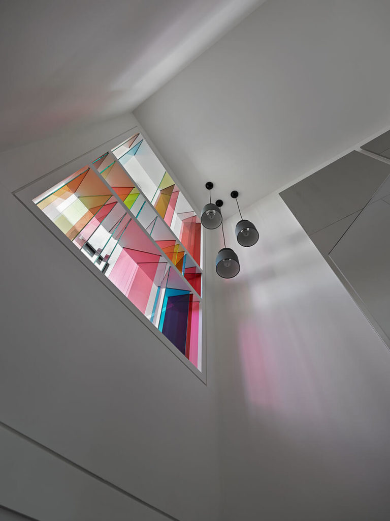 Natural light is projected through the glass, utilizing the white wall as a stage for the play of light across it. The same light makes a drastically different, but equally beautiful, display on the black staircase Looking up at the opening, you can see the colored glass is set at different angles to create different shapes of color.