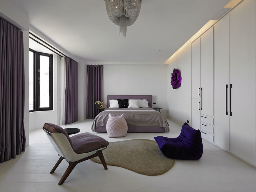 The primary bedroom includes bold and muted shades of purple to liven up the white base of the room. The area in front of the bed was designed for reading and relaxation while enjoying the view from the large bay window of the mountainous landscape outside.