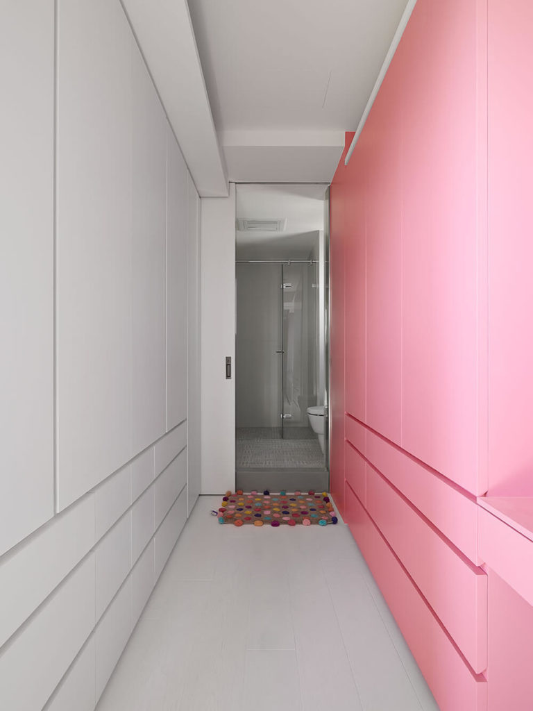 The wardrobes in the kid's room. The entire room is done up in white and pale pink, as the wardrobes display. They are exactly the same design and space, despite the color difference. Beyond them you can see the attached bathroom.