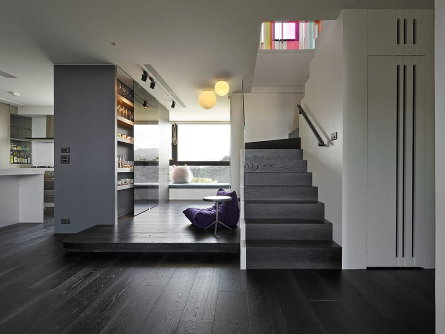 The black stairs against the light wall help create a visual path up to the second floor. The space next to the stairs was designed to be utilized as an indoor play area for the two kids. The existing pillar in the house was changed to a cabinet to hold the resident's cup collection and hold the oven in the kitchen. The reflective gray glass hides the storage while also showing off the landscape beyond the window and reflecting more light deeper into the house.