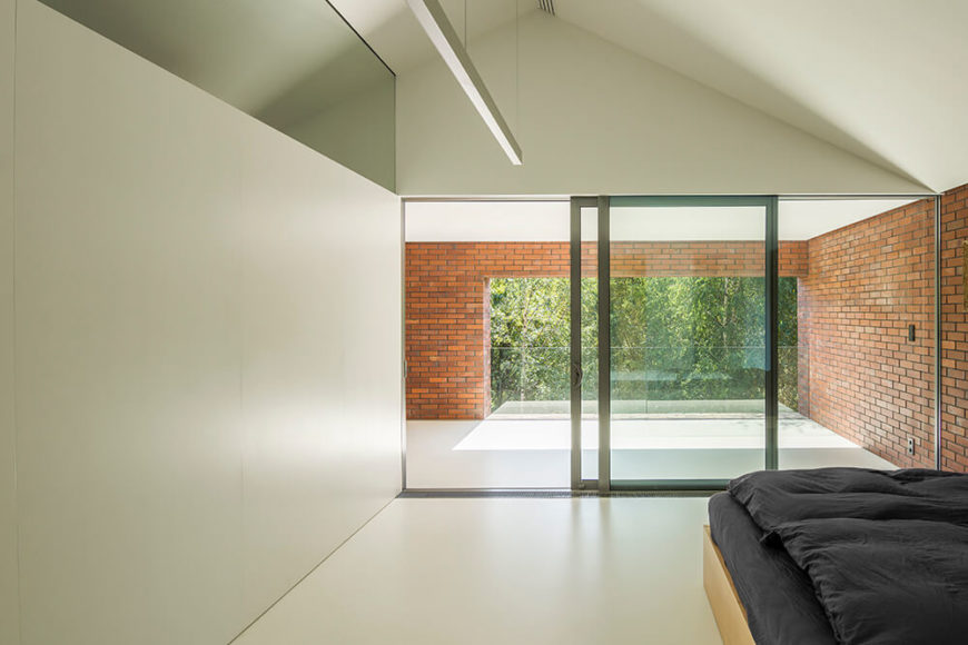 Like most of the private areas of the home, the bedroom is white and minimalist, with only the essential furniture. Sliding glass doors lead into a private covered terrace surrounded by rich red brick.