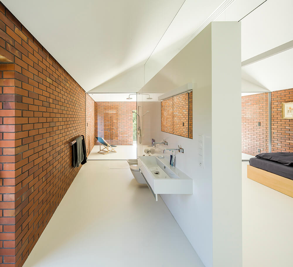 Galley bathroom with a left brick wall and white flooring. It includes an open shower area with a glass divider and wall mounted porcelain sink.