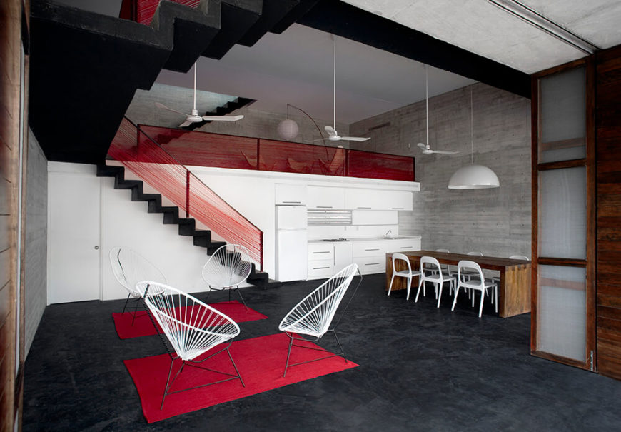 The interior of the house is brightened with bold splashes of red and natural wood accents. The compact kitchen can be seen against the back wall. This simple palette allows for the color and life of the outdoors to stand out.