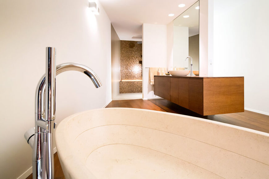 The large bathroom is an exercise in spare but bold detail, with a floating natural wood vanity hosting a white vessel sink at right, and the walk in shower beyond. The large pedestal tub features floor mounted plumbing.