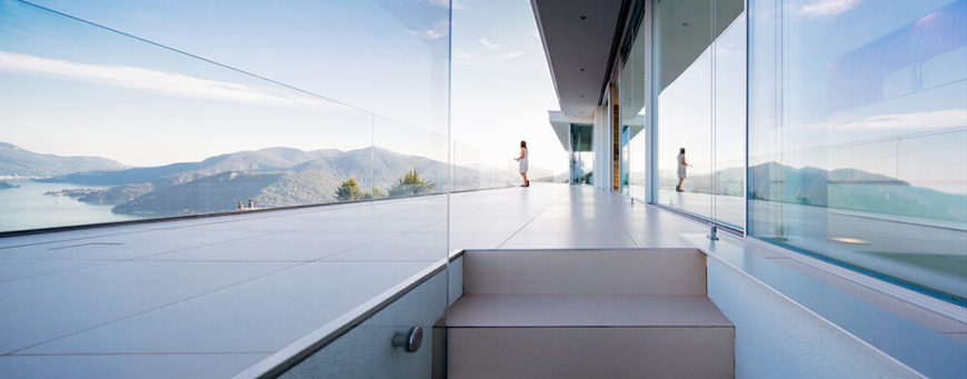 This low view of the upper terrace showcases the glass balustrade and vast open space available when stepping out of the living room. The sleek and unobtrusive floor tiling helps keep the focus on the breathtaking views.
