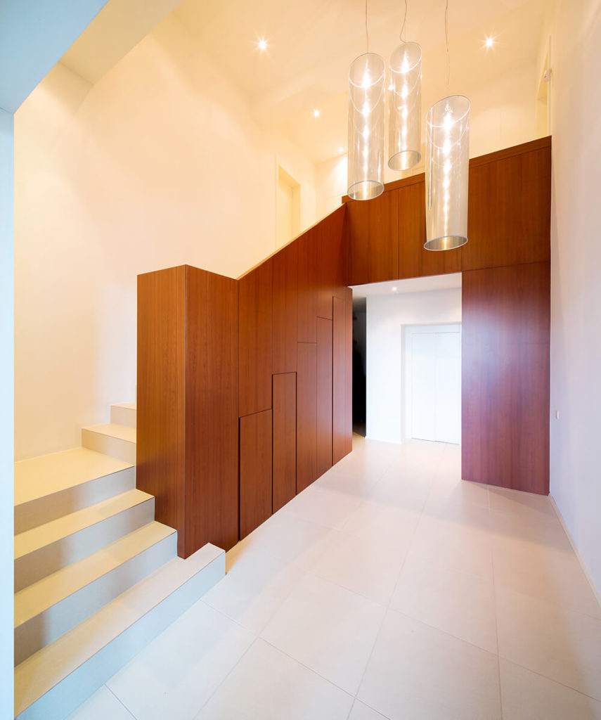 Here's a look at the grand foyer, a resolutely minimalist space informed by rich wood paneling that conceals a set of storage beneath the stairs. Tubular chandeliers offer a sparkling bright presence over the expanse of white tiling.