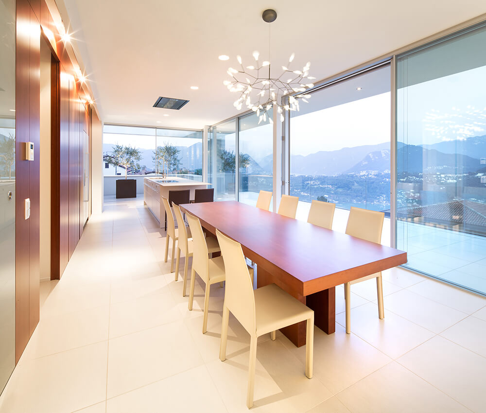 Enjoy a mesmerizing mountain view through the glass walls of this dining area. It has a long wooden table with white chairs and lighted by a fancy chandelier.