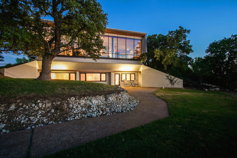 This is an exterior shot of the back of the house, showing off the panoramic windows of the second floor that overlooks the backyard and the landscape beyond.