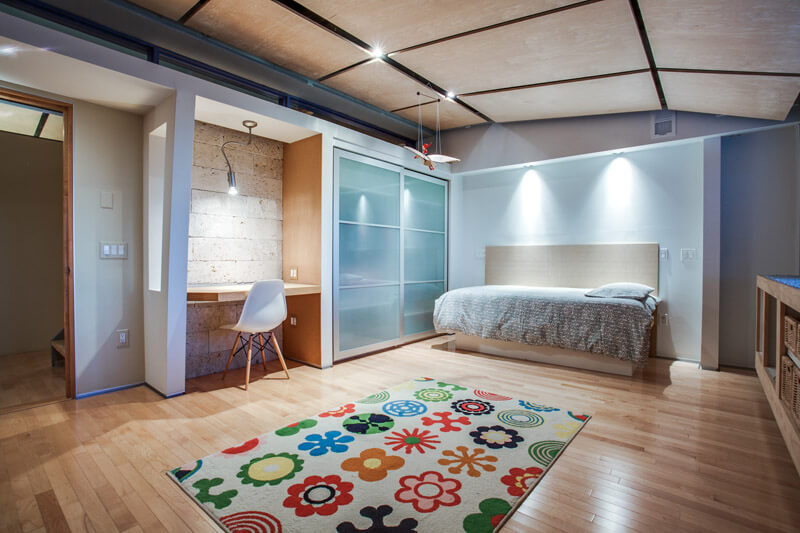 This bedroom on the lower level features a decorative stone wall that was salvaged from the Fort Worth Amon Carter Museum. The wall is comprised of local Austin shell stone and provides warmth and visual appeal to the underground space. Bright colors and plenty of lights help balance the lack of windows in the lower level.