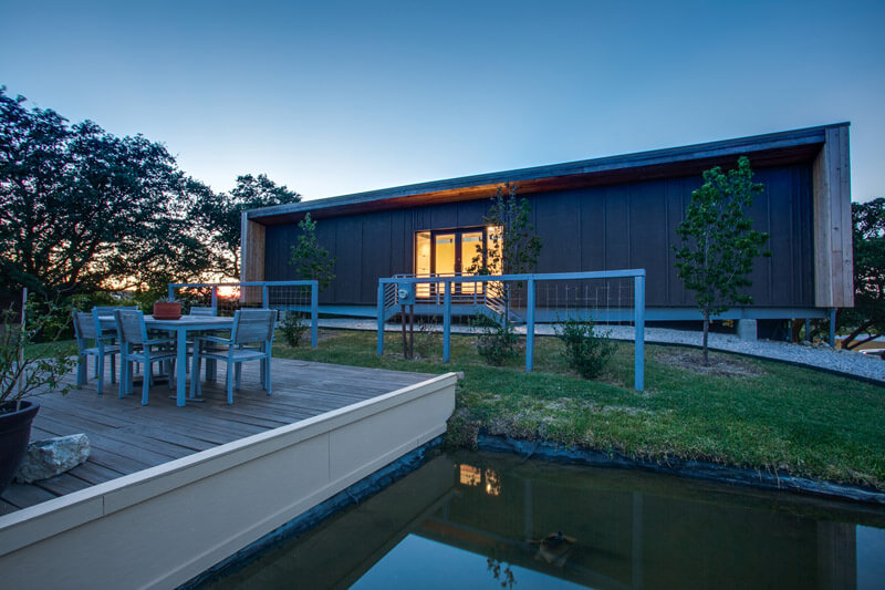 """The front of the house includes a deck for outdoor entertaining and a charming pond with water feature. The exterior of the house features a """"double skin"""" cork finish. This means that the concrete walls are covered in a layer of cork with air space behind it to allow air to flow through it and help to keep the house cooler."""