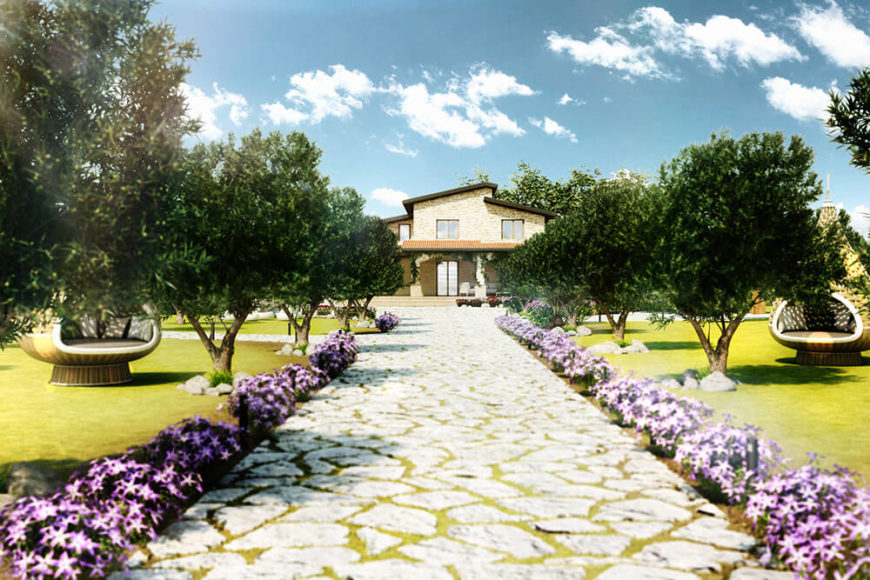 Approaching the villa along a flower-lined stone path, we can see the surrounding landscape is dotted with a carefully laid arrangement of trees and manicured lawn. The home itself stands in the distance in light stone hues.