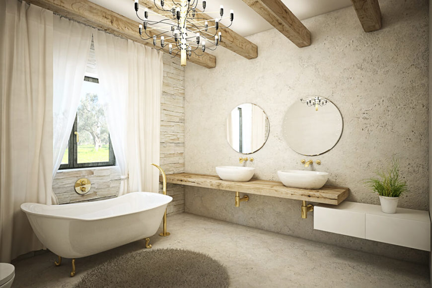 The primary bathroom is a large, luxurious space appointed with gold plumbing and a floating dual vanity in natural wood, with a pair of vessel sinks. The claw foot tub stands next to a window and beneath a modern chandelier.