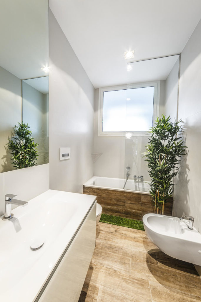 A clever idea for the bathtub, an artificial grass like section is featured where you would step out of the shower, to catch some of the water and ensure that the hardwood floor is not damaged. A large sink is featured below the mirror, and a bidet stands at right.