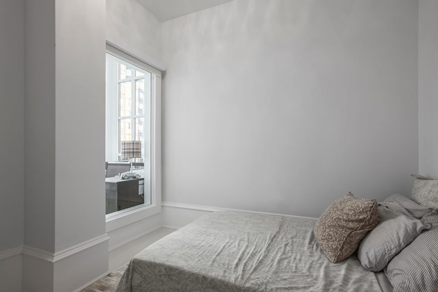 The guest bedroom is laced in the same egg white walls as the rest of the home. Located on the inner part of the home, a window to another room aids the guest bedroom into receiving natural sunlight.
