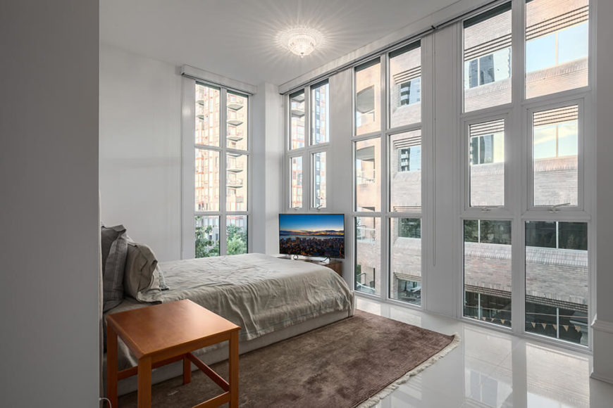 The primary bedroom is located on the outside of the building, and is surrounded by large windows. The area is very minimalist, and doesn't require a lot of furniture for a truly spectacular design.