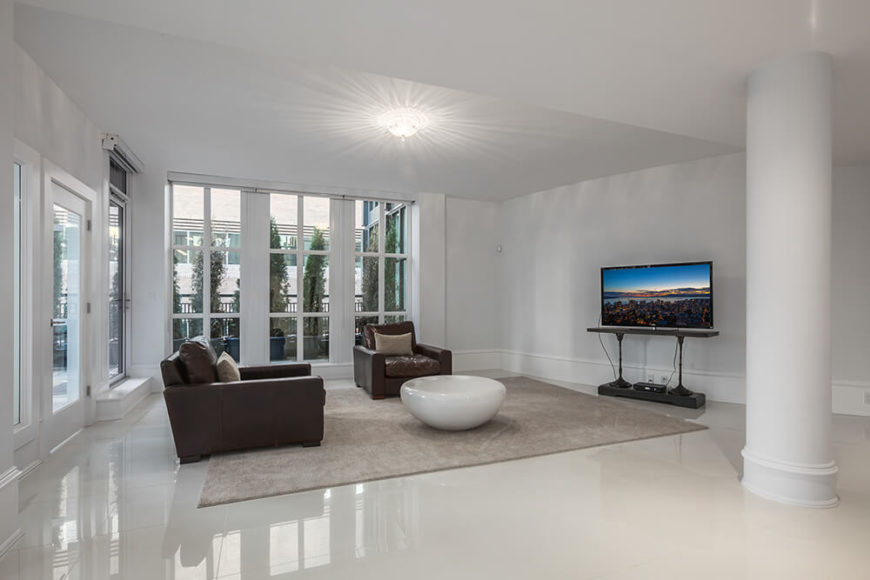 Here we can see a different angle of the minimalist living room. Towering windows line the outside walls for natural light to enter and add a rich organic glow to the room.