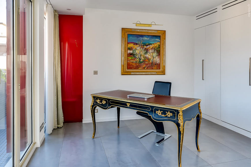 The office space proves it's glory with a large antique desk and classic painting on the smooth white walls. A shocking touch of red hides the entrance to the bathroom.