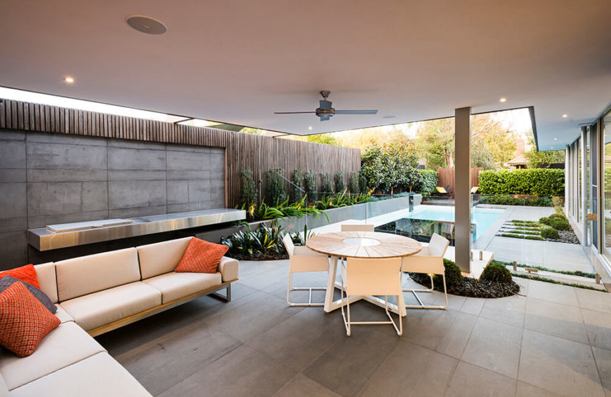 back patio, or alfresco area, features a sitting and dining area. Along the concrete wall is a stainless steel bar with an integrated Electrolux grill. A glass fence separates the alfresco area from the pool area of the backyard.