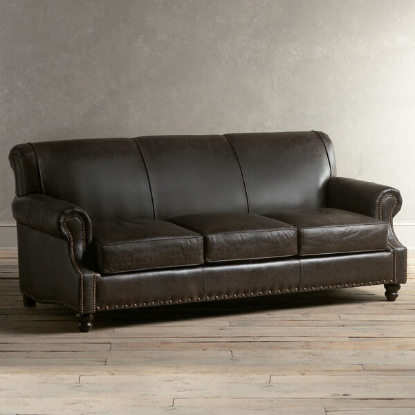 This bespoke dark mocha toned leather sofa is perfect for any traditionally appointed man cave. The arrowhead feet and nailhead trim add a sense of sharp detail while the broad, smooth backing adds an open, minimalist face that emphasizes comfort.