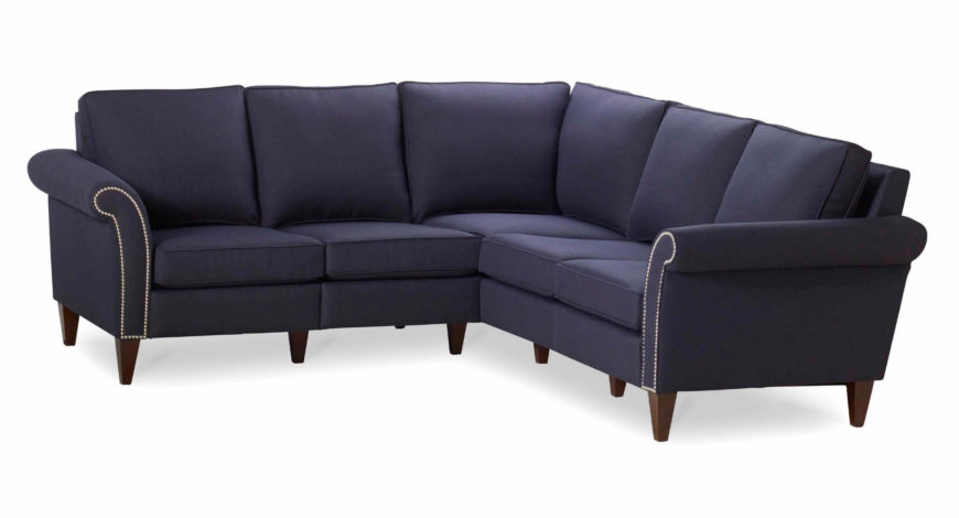 This striking sectional sports a bold navy blue tone, contrasting with the bright nailhead trim on each end, reaching into the elegant roll arms. Subtle dark wood legs support the deeply cushioned but unfussy design.