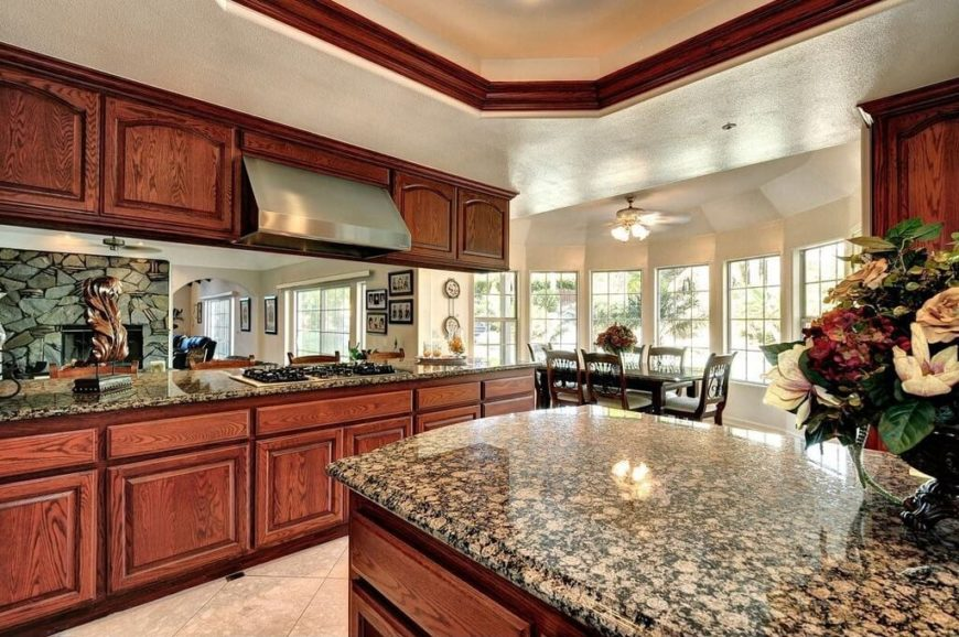 Stunning granite tops these counters and balances the dark grain of the cabinet fronts. Crown molding in the recessed ceiling matches the hue of the cabinetry, carrying the look up to the ceiling. The open design of the cabinets allows one to see out into the rest of the house.