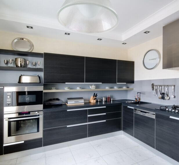The other side of the same kitchen, upper cabinets take up more of the space but open shelving on the far side backed by the grey backsplash helps to break up the amount of black. More stainless steel continues the modern feel of the room.