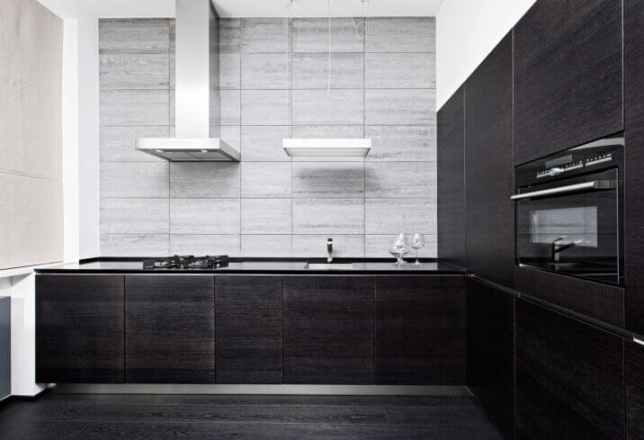 An extensive use of dark cabinets and dark flooring warrants the use of white and light colors on the walls and ceiling to keep the dark hues in check.
