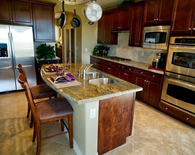 Bold cabinets and sleek stainless steel appliances work to complement the various colors in the granite counters of this charming kitchen. Natural light highlights different colors in the cabinets.