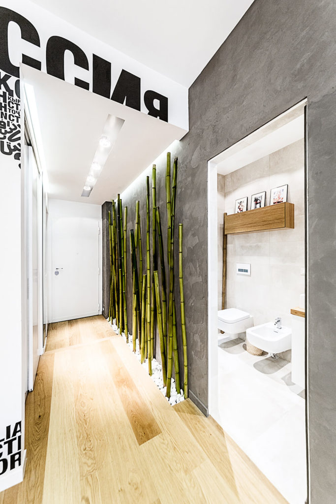 Moving back toward the entryway, we see the camouflaged door opened, revealing a bright bathroom. The sleek wall panels that allow for this invisible doorway help the home feel unified in style and shape.