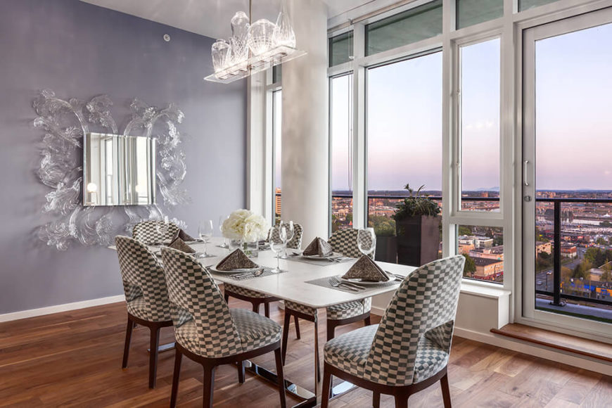 Speaking of the view, here we can see the expansive outlook from the dining area within the open-plan center of the home. The white and stainless steel table stands beside an ornate glass framed mirror, one of many stylistic flourishes in the home.