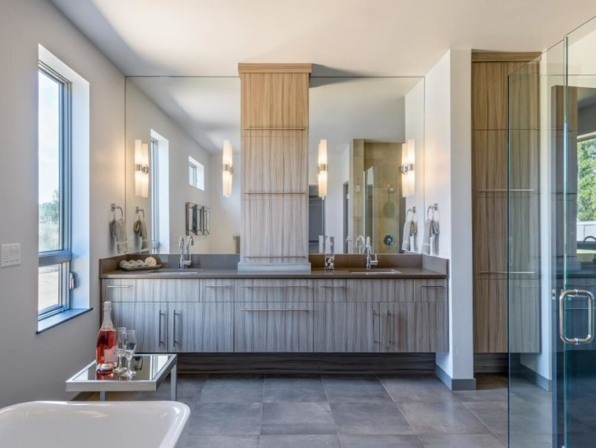 The primary bath sports light wood cabinetry matching that found in the kitchen, which contrasts with a glass enclosed walk-in shower design. The bathroom also plays host to a traditional free standing pedestal tub in white.