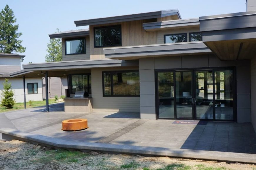 The rich tile flooring of the patio nicely meshes with the light natural wood and concrete surfaces of the home. Large windows and glass doors are framed in black, for a splash of contrast.