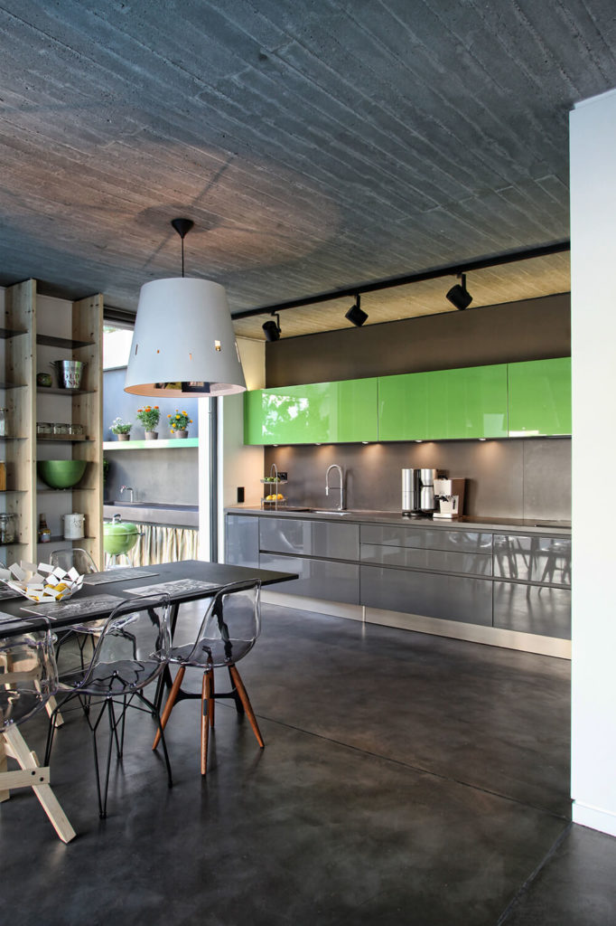 The open kitchen is modern and streamlined all done up in shades of gray, bright spring green, and stainless steel. Part of the dining room can be seen here opening right into the kitchen space.