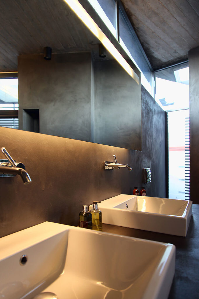A dual vanity takes up the other side of the bathroom. Square white sinks contrast the dark walls and concrete ceiling of the room. The long mirror helps to break up the space even more.