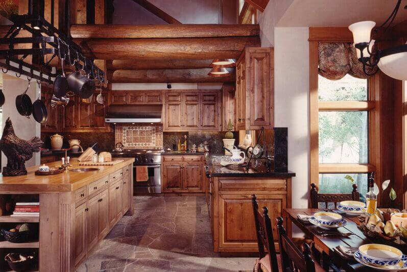 A more rustic kitchen featuring exposed beams, natural wood cabinetry, and a long, all wood kitchen island with a small central sink in brushed nickel.