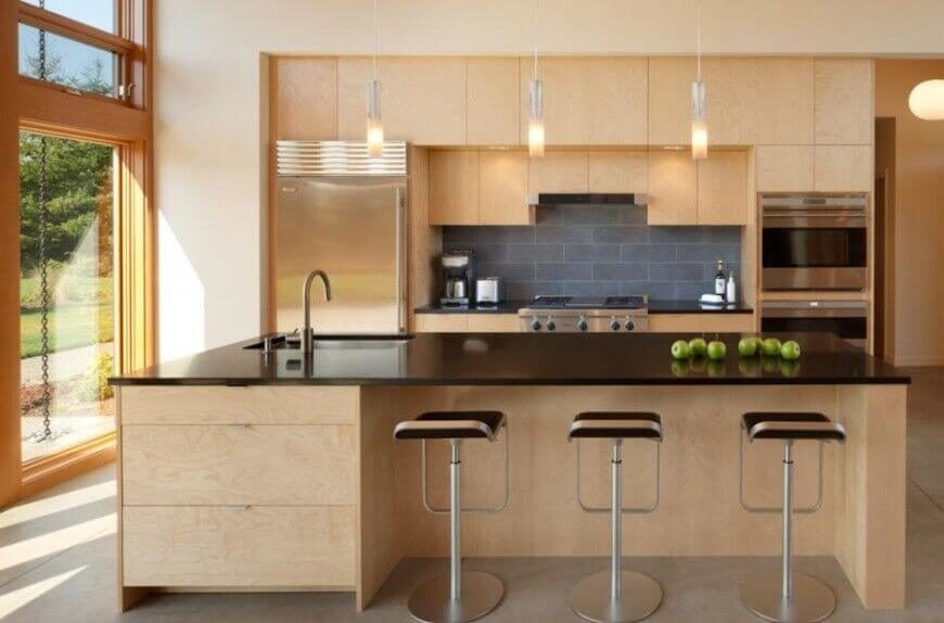 The sleek, glossy black countertops of this island match the landing pads on either side of the stove, and complement the charcoal gray subway tile backsplash