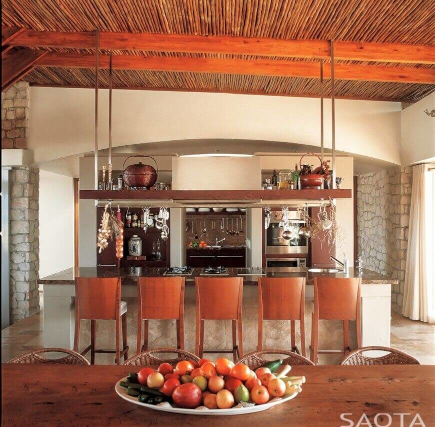 A lovely kitchen with stone accents and a rustic contemporary atmosphere. Above the lengthy island is a large pot rack with drying herbs.