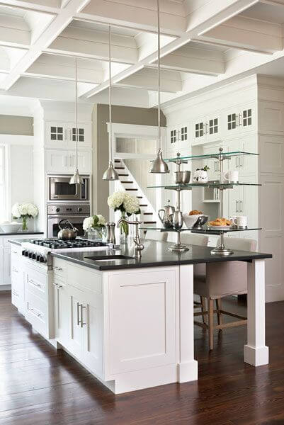 A black and white kitchen with glass shelving, pendant lights, and an elegant coffered ceiling.