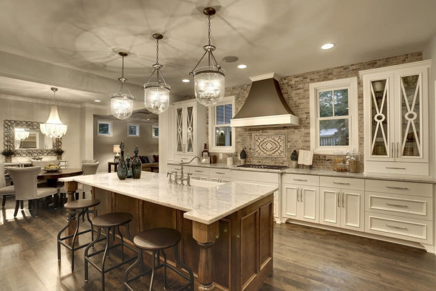 An elegant white and wood kitchen with a stone backsplash and glass-faced cabinets on either side of the main set of cabinets. The eat-in island also includes a large farmhouse sink.