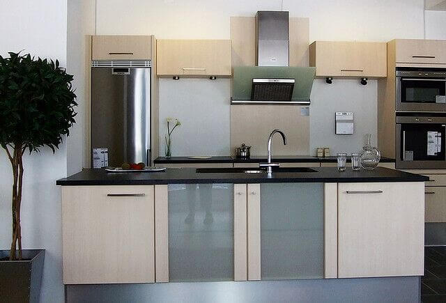 This lovely modern kitchen features a galley layout with a spacious, but not deep island featuring an enormous sink. The island also features frosted glass doors for extra embellishment.