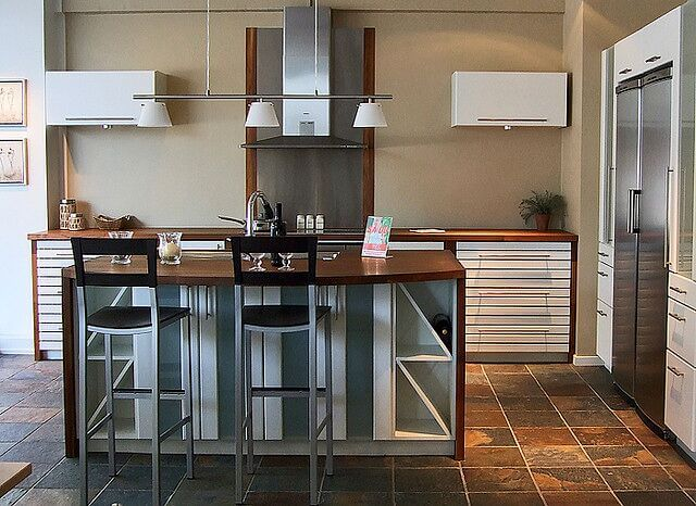 This lovely island features a central sink, a bar for two, and wine racks on either side. The wooden countertop runs down either side of the island.