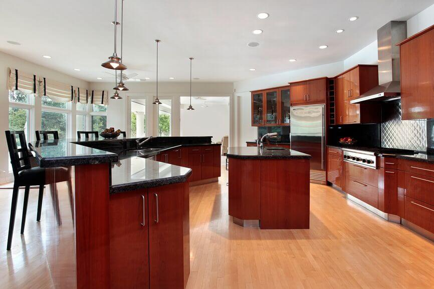 The rich cherry wood of this kitchen contrasts with the light wood flooring and the dark granite countertops.