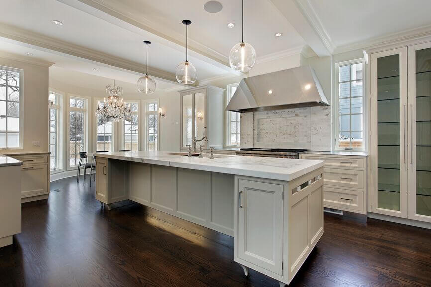 A lengthy white island with marble countertops and a space that would be excellent as a breakfast bar. Above the island are three matching globe pendant lig