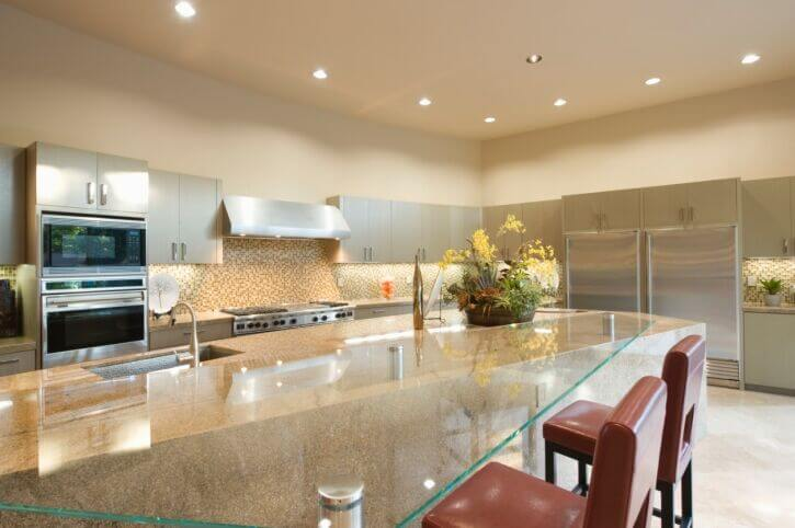 A fantastically unique kitchen with an enormous eat-in island that is partially granite, with an expansive glass eat-in bar.