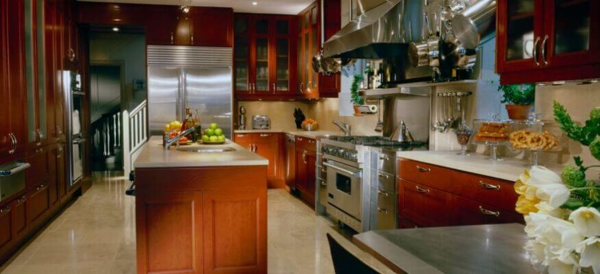 A rich wood kitchen filled with high end stainless steel appliances, greenery, and a lengthy island with an extra rinsing sink.